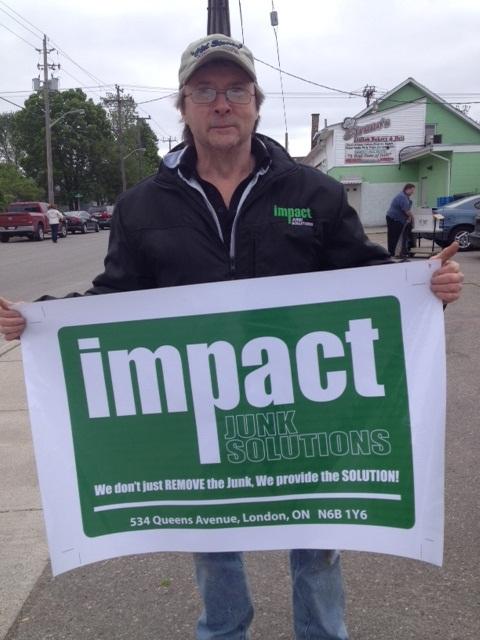 Un bénévole en face du bâtiment d'IJS tient une grande affiche d'Impact Junk Solutions. Sur l'affiche, il est écrit : « Impact Junk Solutions. Nous ne faisons pas seulement le RAMASSAGE des rebuts, nous offrons la SOLUTION! 534 Queens Avenue, London ON N6B 1Y6 ».