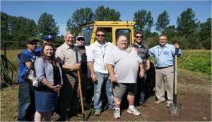 Neuf employés de GreenWorks  dans un champ devant un tracteur jaune. Certains tiennent des bêches et des binettes.