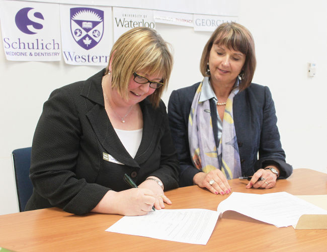Two ladies sitting down and signing the MOU between UWO and Gateway
