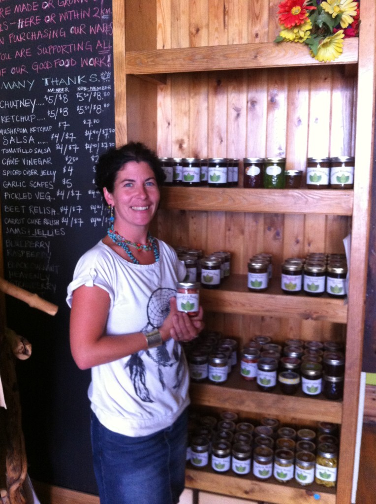 Erin Chapelle, founder, standing in front of shelves showcasing products and holding one sample in her hands.