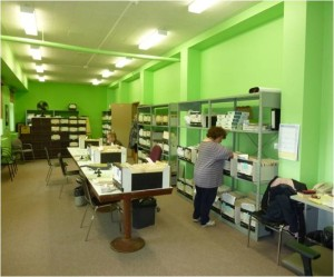 Employee searching through documents at ScanWerks to enter into database. Room contains shelves with books and paper. Room is large, bright, and has lime green walls.