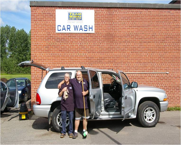 Two Waterwerks staff, holding a rag and mop, standing in front of a freshly cleaned car that has all doors open. The Waterwerks car wash