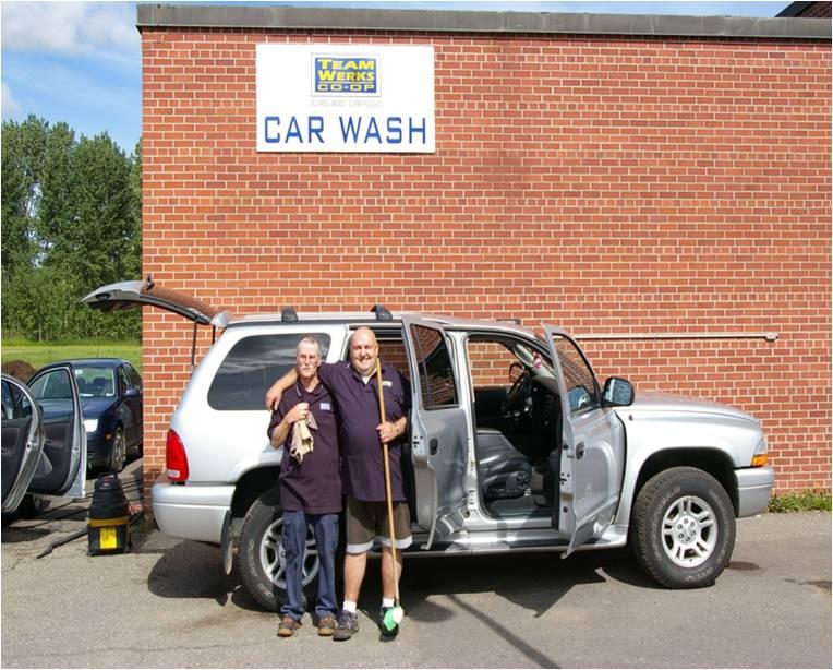 Deux membres du personnel de Waterwerks, tenant un chiffon et une vadrouille, devant une voiture fraîchement lavée aux portes ouvertes. Le lave-auto WaterWerks
