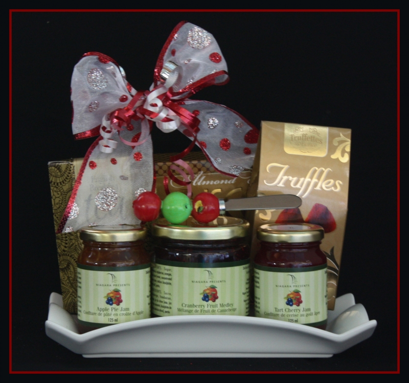 pictured three jams, with a spreader balanced on top of them. Behind the cards are a pack of truffles, tea, and biscotti. There is a bow on the package.