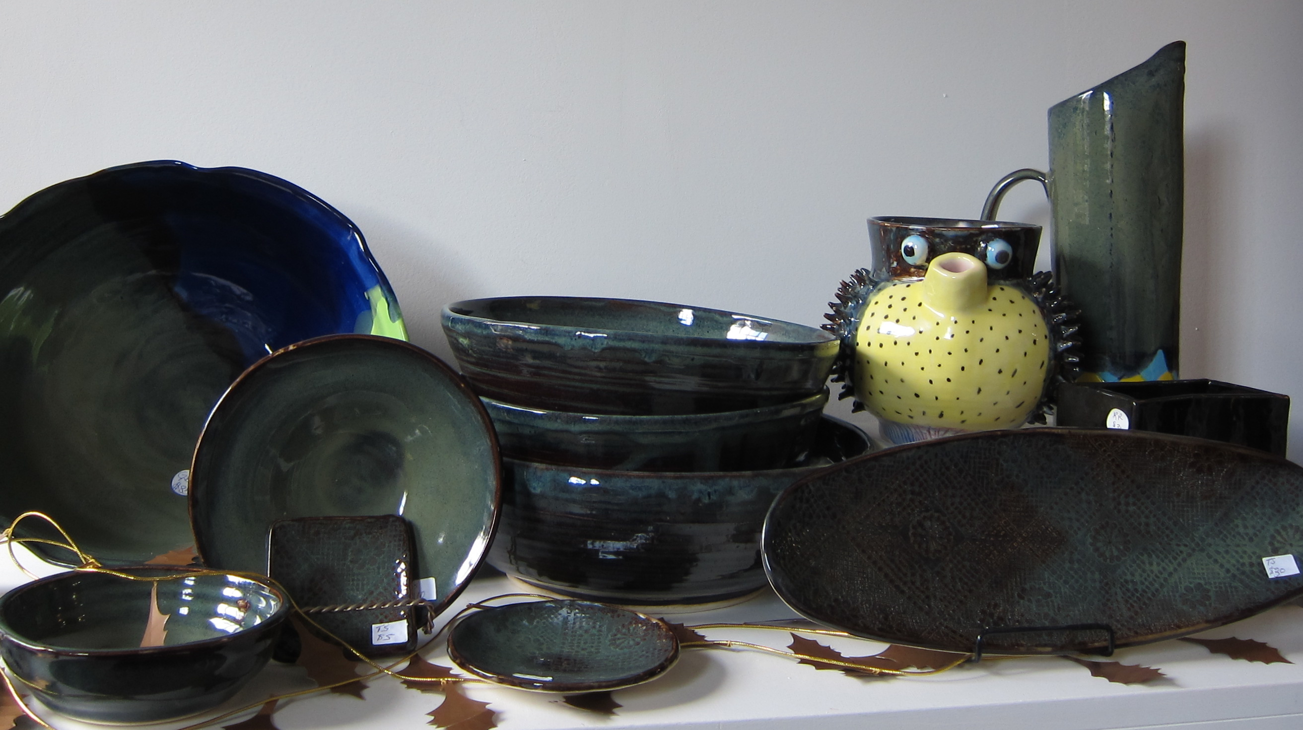 Hand made bowls, mugs, and a puffer fish sculpture, all made by low-income women, can be seen.
