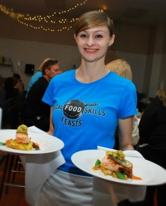 Young trainee carrying two plates of food for a special event. Her bright blue T-shirt promotes the food skills program