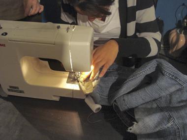 Un gros plan sur les mains d'une femme faisant passer du tissu dans la machine à coudre.