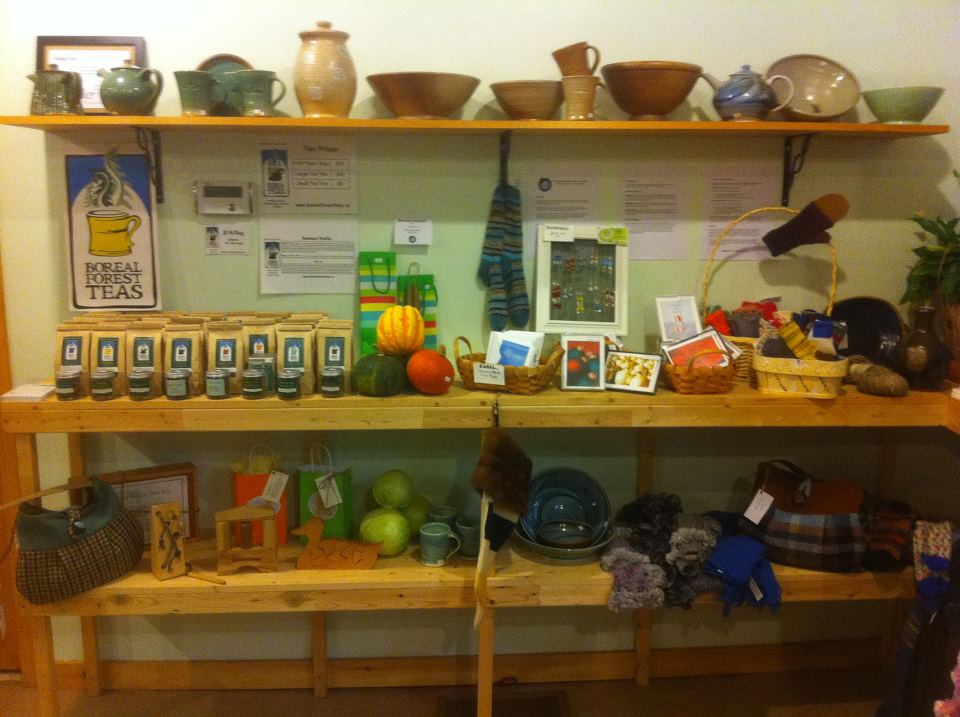 Shelving display of goods for sale at the Truth North Community Co-operative. The top shelf of unit has a variety of pottery. The middle shelf has a selection of teas, crafts, cards, and knit items. The bottom shelf has a mixture of purses, small wooden carvings, pottery, and knit items.