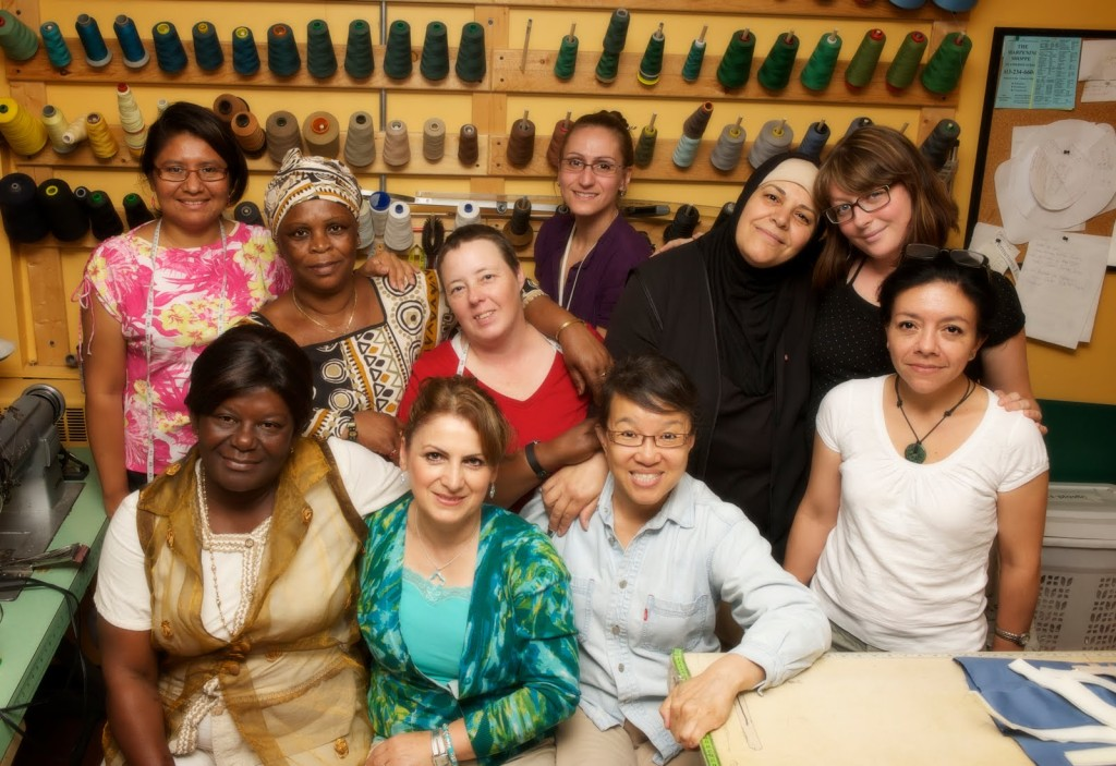EcoEquitable training group of 10 women of many nationalities, standing in front of spools of thread of many colours