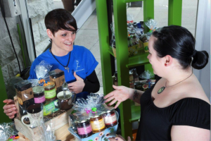 YOU participant in a blue YOU T-shirt is excitedly showing gift baskets that have been made through the YOU program, with jams, teas, mugs and other small things, to customer.
