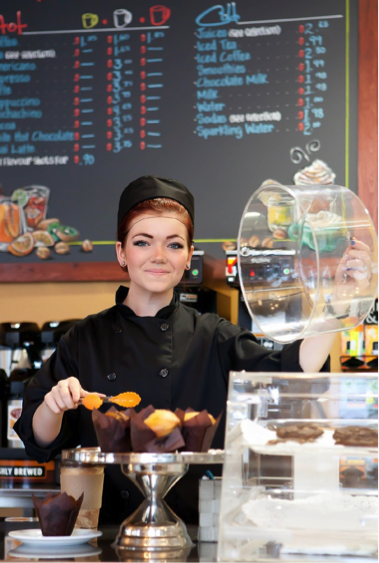 A smiling young YOU participant, wearing the café uniform which consists of a black chef jacket, and a black chef cap, is serving baked goods at the YOU Made it Café.