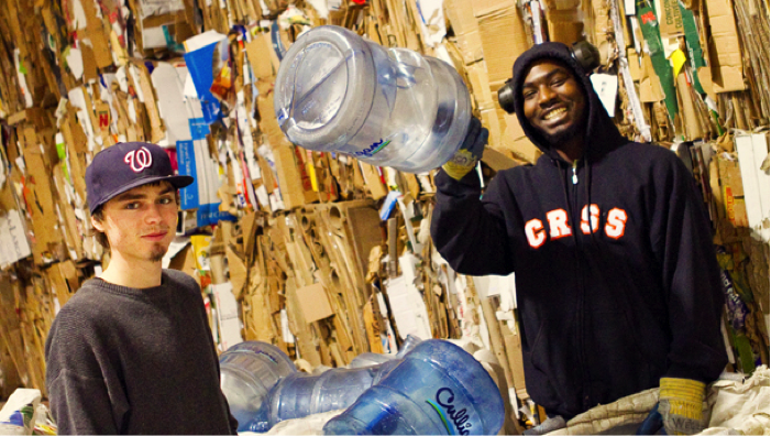Two YOU participants sorting large jugs and other recycling at the YOU Made It Recycling Facility. They are standing in front of a large wall of compressed cardboard boxes, and smiling.