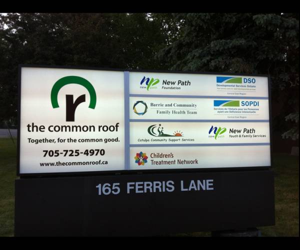 The Common Roof's tenant and address pylon sign outside the building. Address is 165 Ferris Lane. Sign includes images of all tenants' logos and business information.