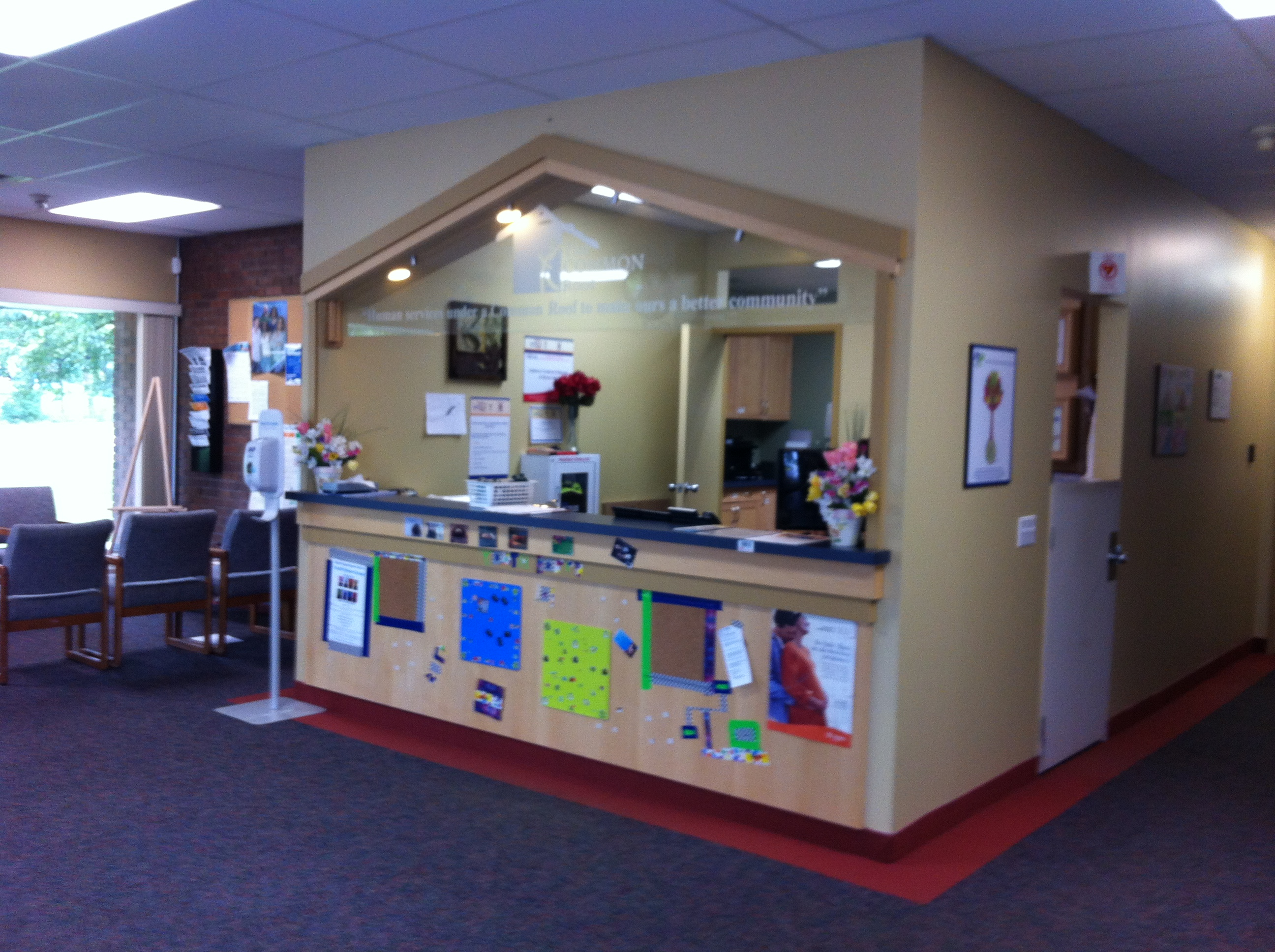 Common Roof Reception. A waiting area with pamphlets can be seen beside a large reception area. The reception desk/area is within a room that is open to the public through a large window and half wall. The half wall is covered in various posters and signs.
