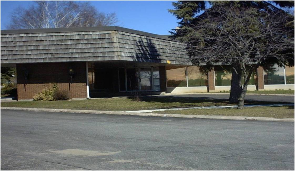 Exterior of original Orillia building. A one story brick building with a flat roof and a shingle overhang. A tree and some grass can be seen in front of the building.