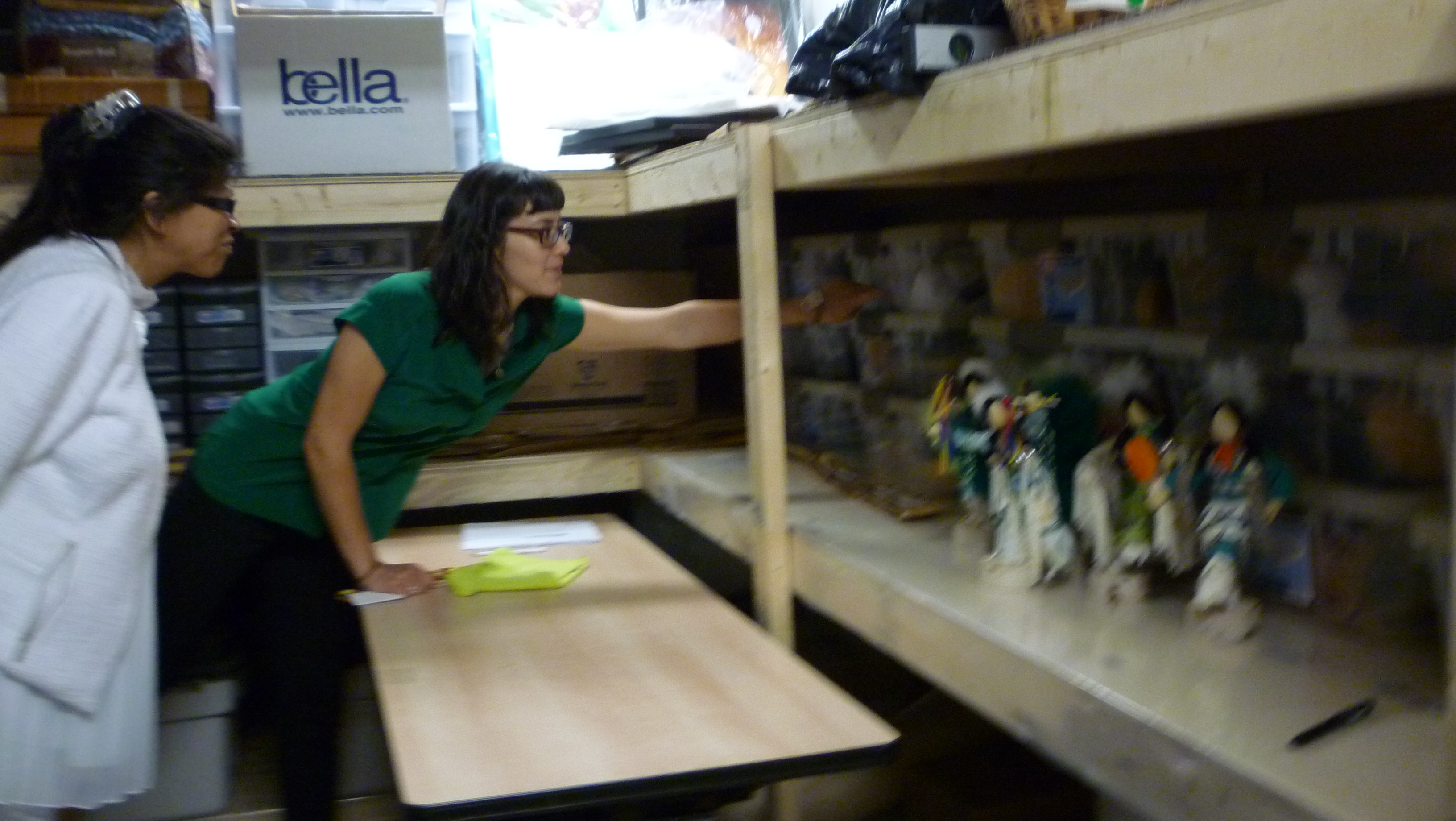 Two women in Kitigan storage are exploring the kind of art stored there