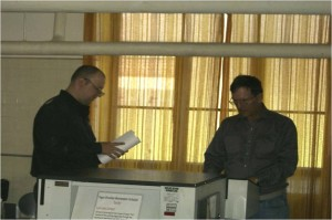 Two employees standing at shredding device shredding documents while working at PaperWerks.