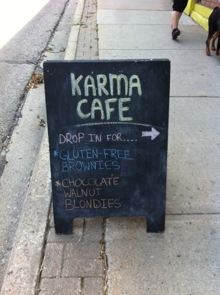 "Outdoor sign welcoming customers to try their unique products, written on small black sign. Sign states: ""Karma Café. Drop in for… Gluten-free brownies and Chocolate walnut blondies."""