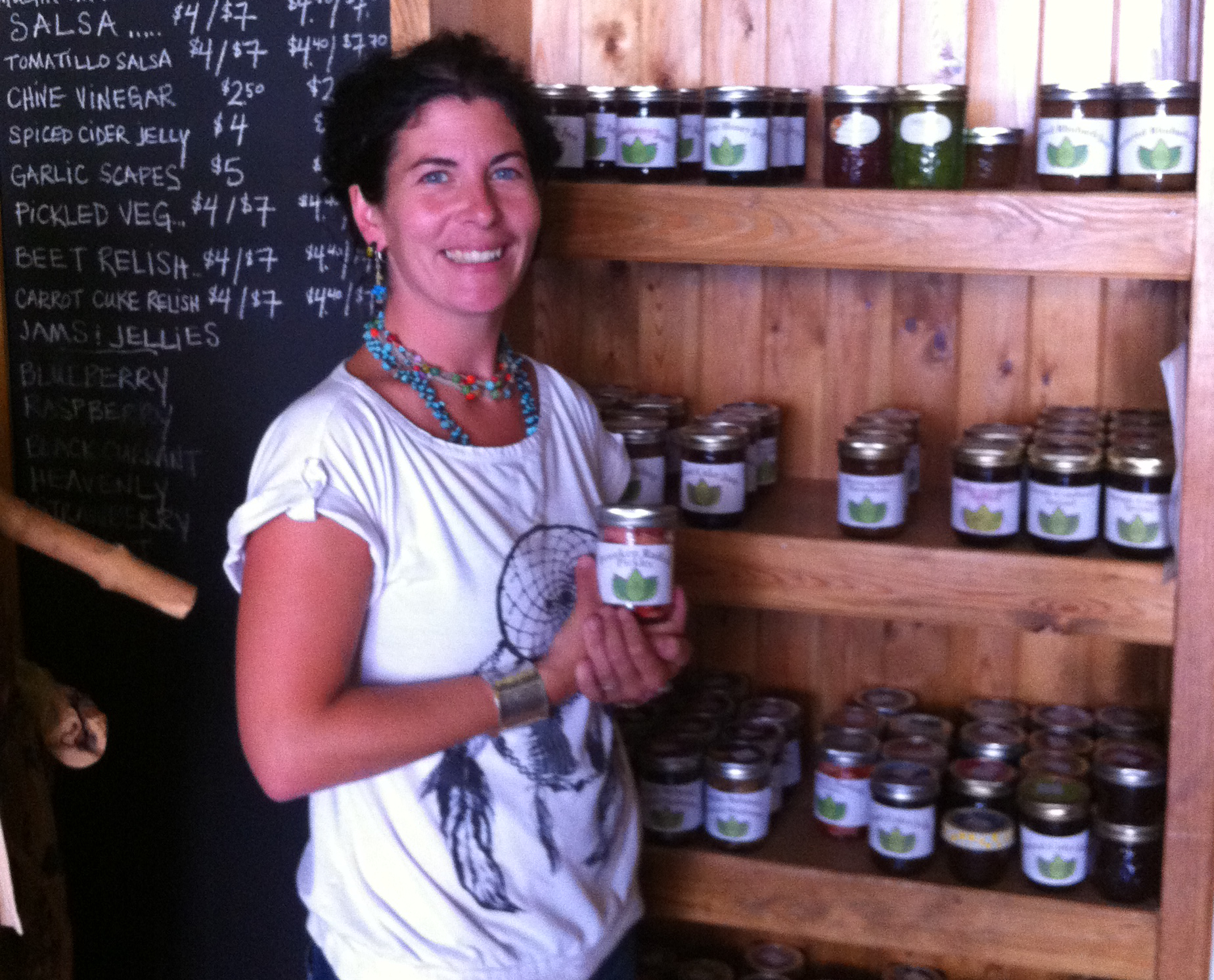 Image of Erin Chapelle, founder, standing in front of shelves showcasing products and has one sample in her hands