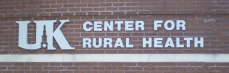 Entrance sign to UK Center For Rural Health Gateway, light blue on brick wall