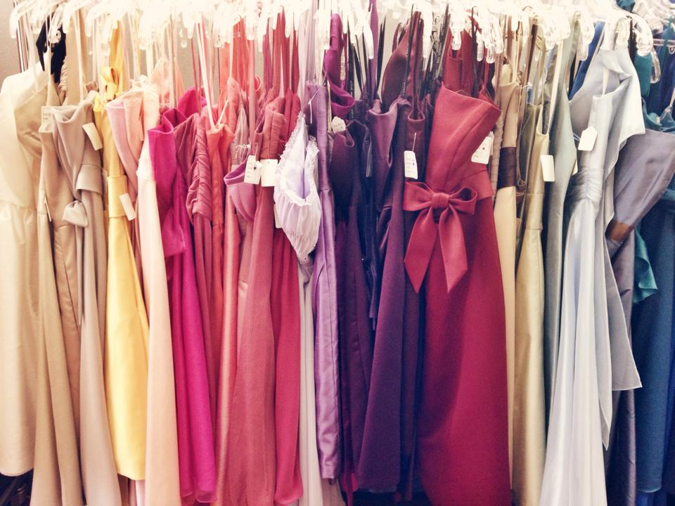 Multiple different coloured cocktail dresses on a store rack ready for purchase.