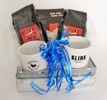 KLINK holiday gift basket. Three coffee bags with two KLINK mugs. They have a blue ribbon bow on them, and are contained in a silver box.