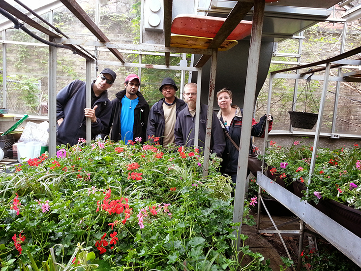 Four workers inside of a lush greenhouse with flowers and vegetation growing around them.
