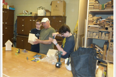 three people in a woodworking room with tools and wood pictures. Two of them are students being trained by a third individual.